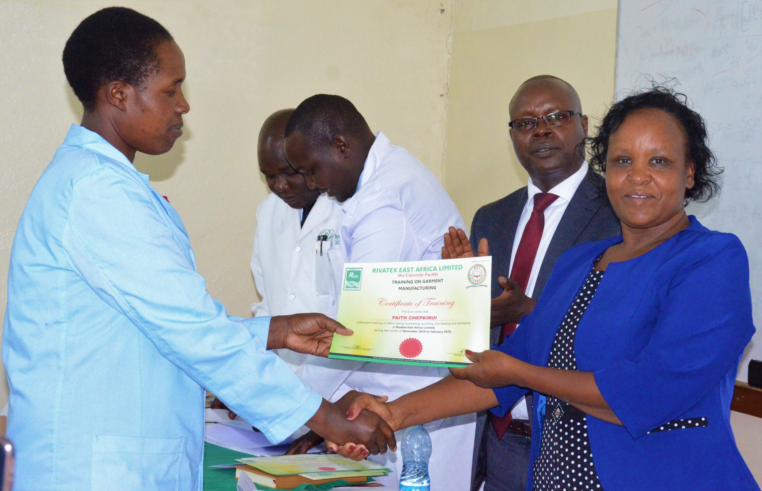 Bomet Chief Executive Committee member in charge of Education Julian Yegon (Right) awards a certificate to one of the trainees after successfully undergoing training at our facility.